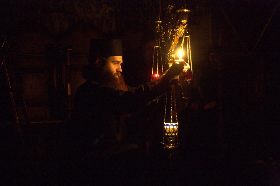 Афонский монах зажигает лампаду у иконы